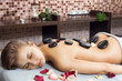 Glad woman receiving a massage with hot stone in a spa center