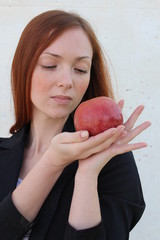 Redhead young woman looking at an apple