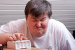 Geistig behinderte Frau mit Tablettenbox blickt traurig