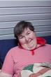 Geistig behinderte Frau liegt im Sessel und lächelt
