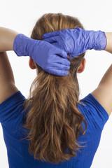 Frau bindet sich die Haare mit blau behandschuhten Händen