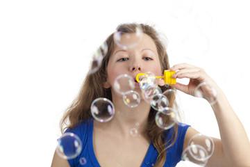 Frau bläst Seifenblasen zum Betrachter