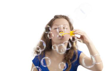 Frau pustet Seifenblasen mit geschlossenen Augen