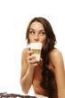 schöne frau trinkt latte macchiato kaffee und schaut zur seite