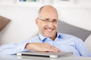 lachender mann mit seinem notebook zu hause