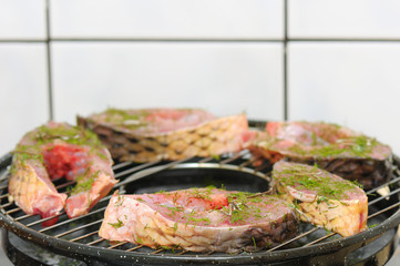 closeup view of fresh fish with green spicies on grill