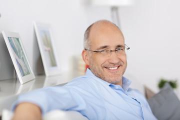 lächelnder mann sitzt entspannt auf dem sofa