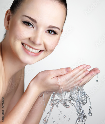 Smiling woman washing  face with water