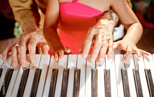 hands of old woman and child playing piano