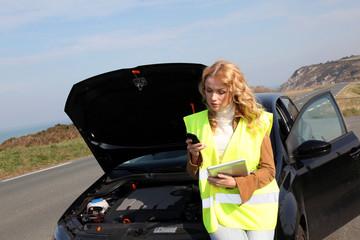 Woman standing by broken down car