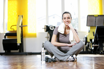 young woman sitting on the gym's floor after workout