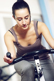 A young woman riding an exercise bike