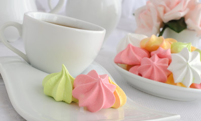 Meringue cookies on a plate with a cup of coffee
