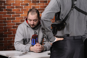 Police officer interrogates detainee