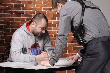 Police officer interrogates detainee