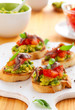 crostini with avocado,tomato and anchovy