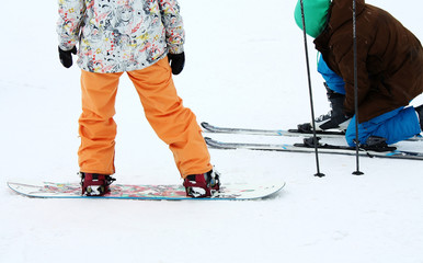 Snowboarder and skier