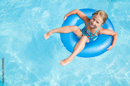 Swimming girl in blue water - space for text