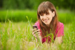 Young woman with mobile phone lies on green grass