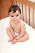 Cute baby sat in cot looking to camera