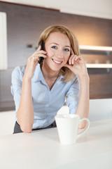 junge frau in der küche mit telefon