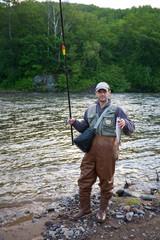 Happy fisherman holds captive salmon.