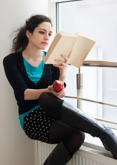 Portrait of a pretty young student eating an apple while reading