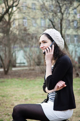 Young woman talking on the phone outdoors in a park