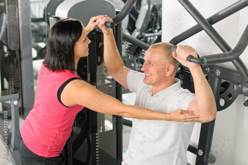 Fitness center trainer assist man exercise shoulder