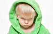 The little boy in green dressing gown looking seriously