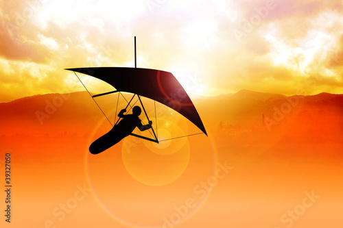 Silhouette of a man figure gliding during sunrise