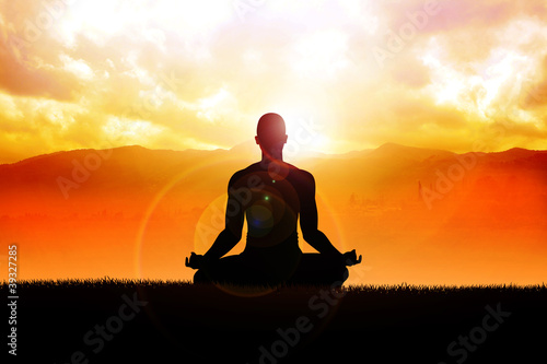 Silhouette of a man figure meditating in the outdoors