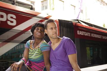 Sitzendes junges Paar im Hintergrund die Straßenbahn