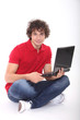 Cute young man sitting and holding laptop