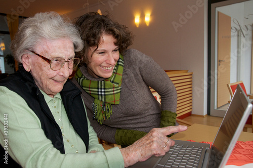 Seniorin am Laptop mit Enkelin