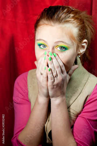 Sad redhead girl closed her mouth with hands