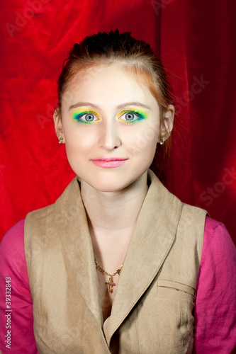 Red-haired girl smiling and writhing with fashion make-up
