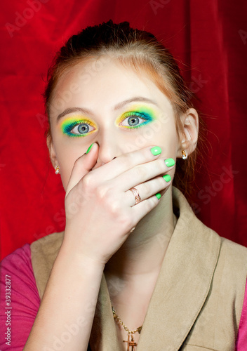 Sad redhead girl closed her mouth with hand