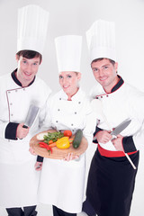 Three smiling chefs holding vegetable board