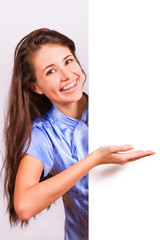 Attractive girl with braces presenting empty board