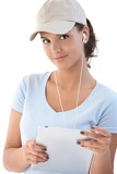 Pretty girl with tablet and earbuds smiling