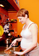 Pregnant woman with cake in kitchen