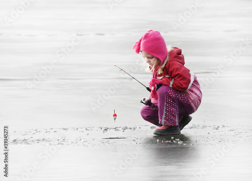 Keuken foto achterwand Vissen Little child fishing on a frozen lake in winter.