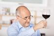lächelnder mann prostet mit einem glas rotwein