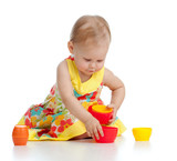 Funny little child is playing with toys while sitting on floor,