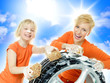 Cute child and young woman cleaning a wheel outdoors