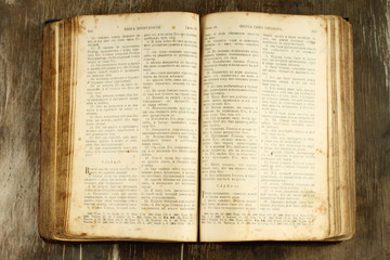Open old Bible on wooden background