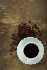 Coffee cup with beans on an old wooden background