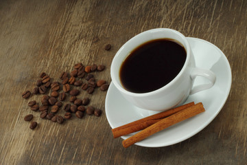 Coffee cup with beans and cinnamon sticks