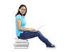Studentin sitzt auf Bücherstapel mit Laptop